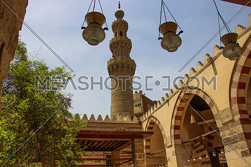 a photo from the yard of the blue mosque in old Fatimid Cairo (sonkor ) showing the architecture style, lamps for lighting , Egypt