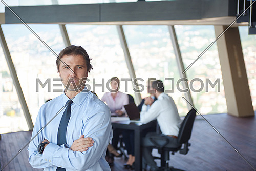 handosme business manportrait  at modern bright office indoors with his team in group working together in background