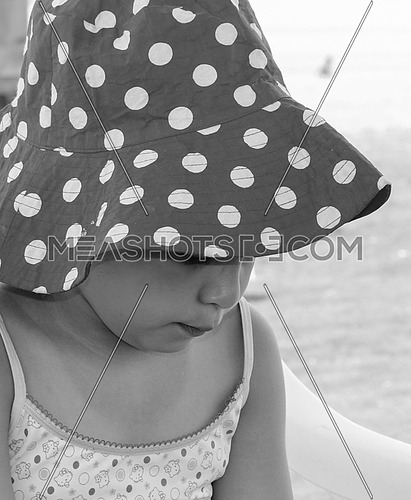 A little girl wearing a big hat on the beach in black and white.