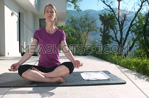 Woman practicing Yoga in front of luxary mansion