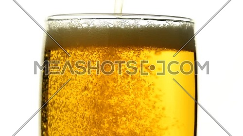 Close up background of pouring beer with bubbles and foam in glass, low angle side view, slow motion