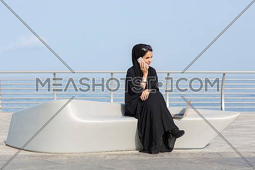 Saudi woman setting and talking to her phone in public