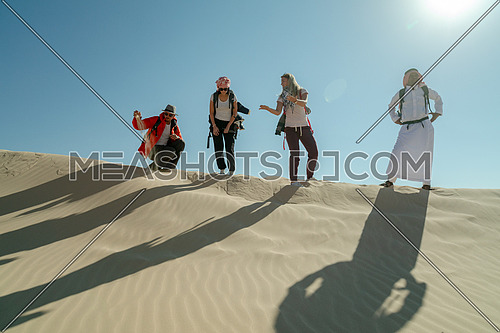 Group of tourists standing on the sands with bedouin guide while exploring Sinai Trail in Ain Hodouda by day.