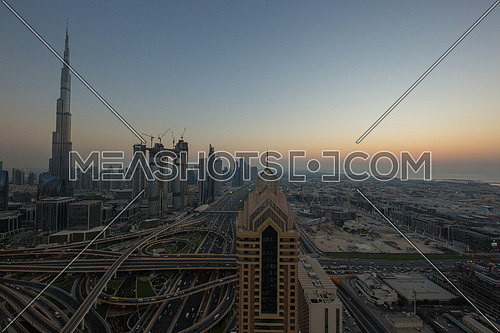Long shot for Dubai City showing Burj khalifa in background and Roads at sunset.