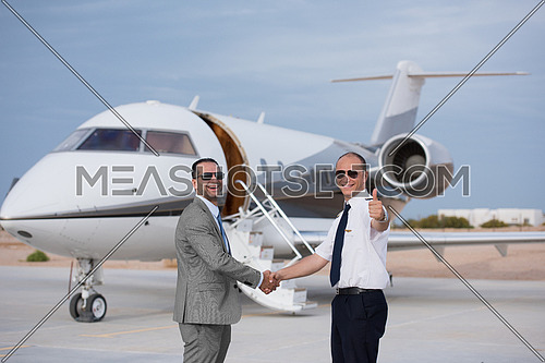 portrait of middle eastern pilot and successful businessman shaking hands in front of private airplane