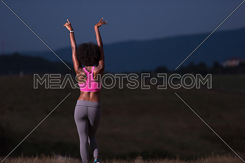 Young beautiful black girl laughs and dances outdoors in a meadow beautiful summer night
