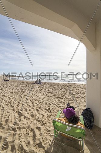 Cadiz Spain- April 1: Caleta beach in the middle of the old city is the most popular of the beaches, Group of young people enjoying a sunny afternoon sitting in the sand, take in Cadiz, Andalusia, Spain
