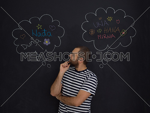 young future father thinking about names for his unborn baby to writing them on a black chalkboard