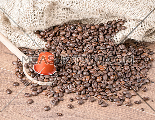 Coffee capsule on wooden spoon and roasted coffee beans with burlap sack on wooden background.