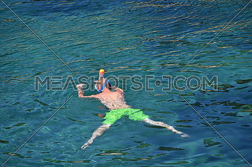Young man swimming underwater and diving in blue sea water with snorkel mask, rear view