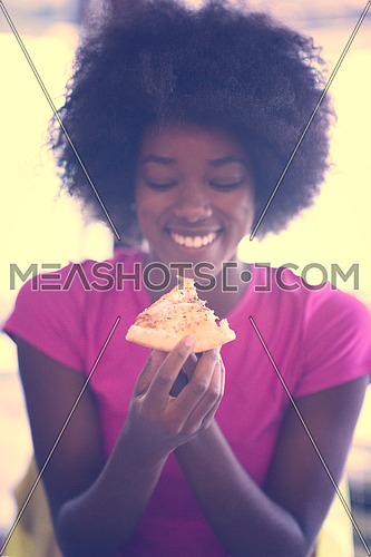 young very hangry african american woman with afro hairstyle eating tasty pizza slice in fast food restaurant