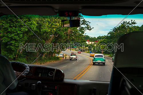 Looking through car window to road, wonderful view of old cars typical of Cuba and a moment of real life.