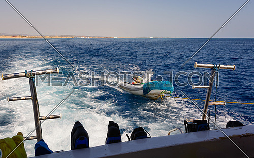 In the picture a moving ship , docked with a speedboat ,at forward  hooked  flippers and masks for snorkeling and in the background Egyptian coast .
