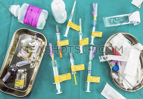 Preparations for parenteral medication in syringes at a hospital table, conceptual image, horizontal composition