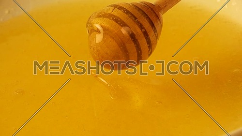 Close up spinning wooden honey dipper spoon in bowl of fresh thick fluid acacia honey, high angle view, slow motion