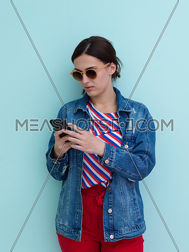 Portrait of young girl using smartphone while standing in front of blue background. Female model wearing sunglasses representing modern fashion and technology concept