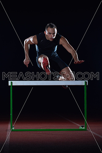 man athlete jumping over a hurdles on athletics race track
