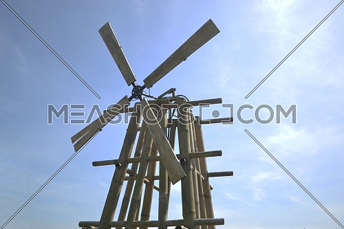 Vintage wood and bamboo propeller with a gear wheel on a blue sky background