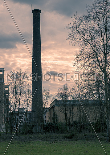 In the picture a large chimney located close to homes, split toning color used.