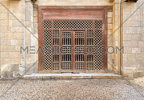 Wooden ornate door over stone brick wall, Old Cairo, Egypt