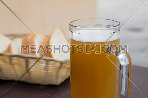 One glass of unfiltered craft draft wheat weizen beer and sliced bread on wooden table