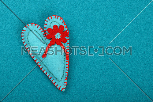 Felt craft and art, one handmade teal stitched toy heart with red flower on blue background, top view