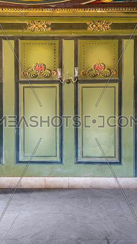 Beautiful elegant carved frames on green wall with ornate border with white marble tiled floor, in abandoned old building
