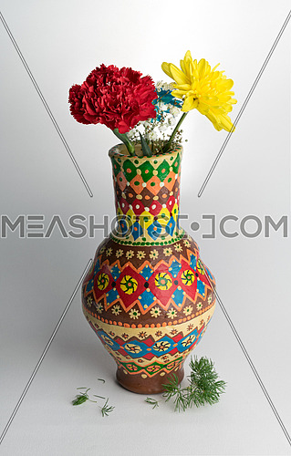 Colorful pottery vase with two flower on white background