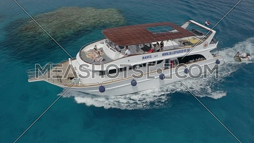 Aerial orbit shot for Girls sunbathing on top Deck of Boat, in Hurghada at day