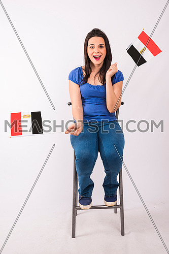 young lady cheering and sitting on a metal chair and holding small egyptian flag
