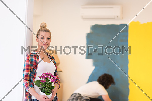 Happy couple doing home renovations, the man is painting the room and the woman hold the pot with flowers