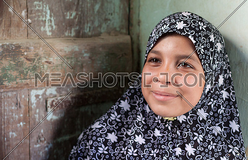 Young girl close to the house door in Fayoum street