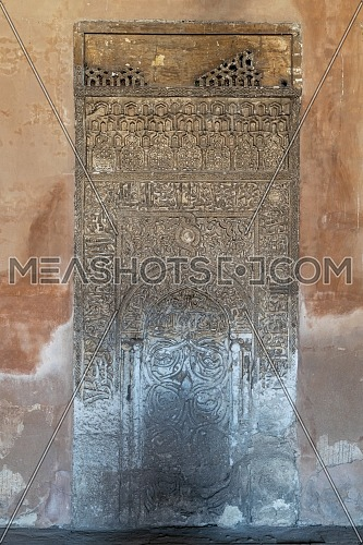 Decorated engraved stone wall with floral patterns and Arabic calligraphy at Ibn Tulun Mosque, Cairo, Egypt