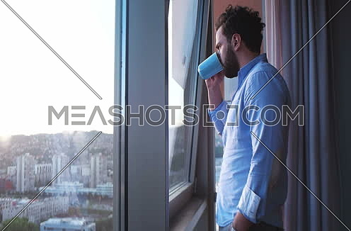 Man in shirt drinking coffee or tea by window admiring greath view on town during sunset