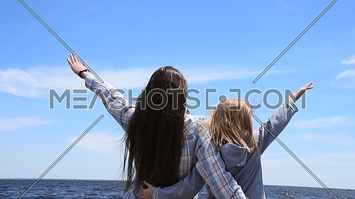 Close up, rear view of young woman and small girl with hands up in clear blue sky over sea water, wind shaking hair, sunny day, low angle view