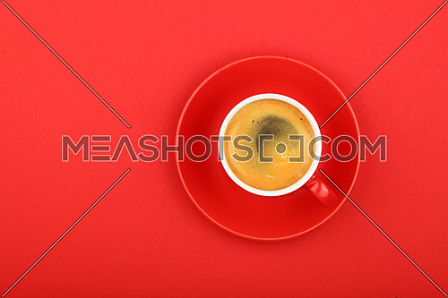 One full morning espresso coffee shot with crema in small red cup with saucer on red paper background, top view, bird eye view