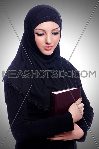 Young muslim woman with book on white