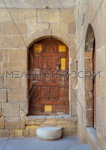 Old wooden door framed by arched bricks stone wall at the courtyard of al Razzaz historic house, Darb al Ahmar district, Old Cairo, Egypt