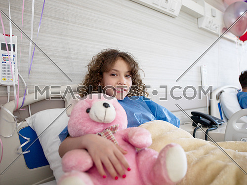 young girl lies in a hospital bed while hugs pink teddy bear