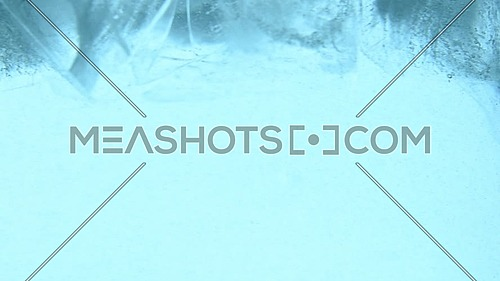 Clear ice cubes with bubbles of air float, spin, whirl and melt in blue water, close up, low angle side view, slow motion