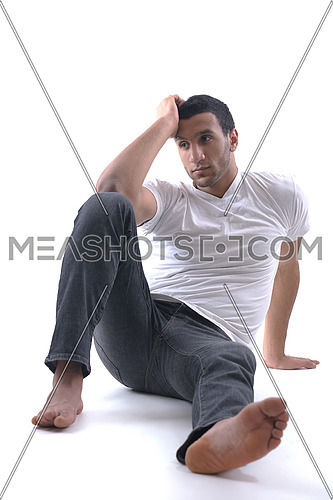 portrait of relaxed young man dressed in white shirt and jeans isolated over white background in studio