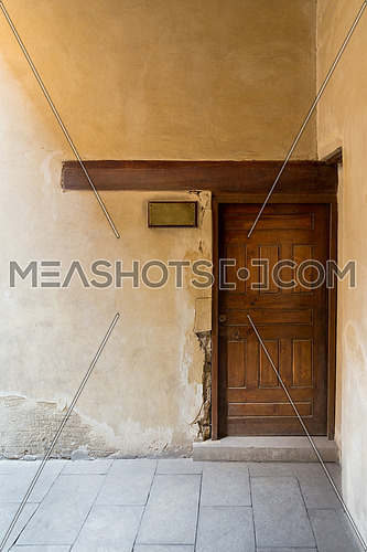 Wooden aged door on grunge stone wall and blank weathered copper door sign, Medieval Cairo, Egypt