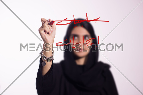 """Arabian middle eastern business woman writing with a marker on virtual screen in arabic """"Negatives"""" """"Positives"""" السلبيات و الإجابيات crossing out the negatives isolated on white background"""