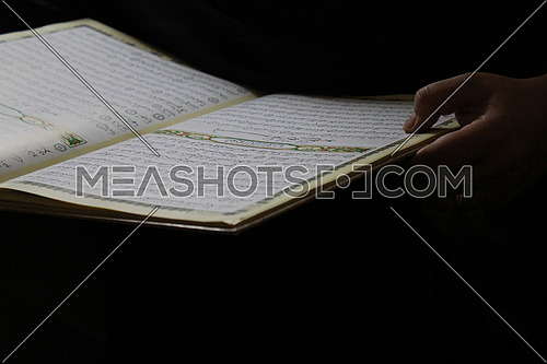 female hand holding the holy Quran book