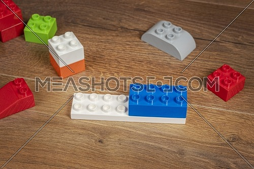 beautiful view on colorful toy bricks on a brown wooden background. Toys in the table