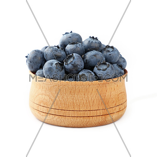 Portion of fresh blueberry berries in rustic wooden bowl isolated on white background, close up, low angle view