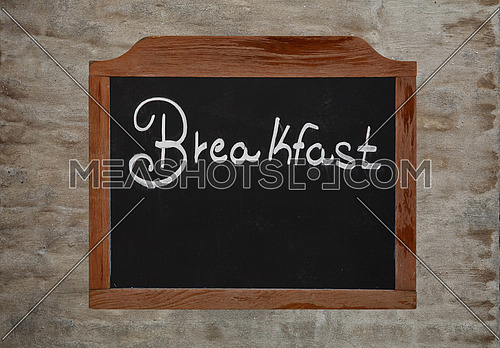 White chalk written word BREAKFAST over old black school chalkboard blackboard sign in vintage brown wooden frame over background of grunge uneven gray daub plaster wall, close up