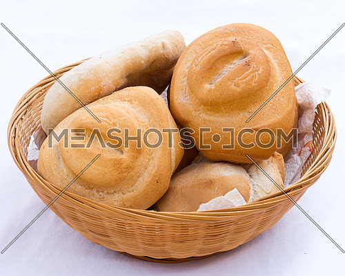 In the picture bread in wicker basket isolated on white.