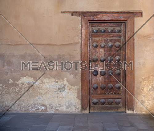 Grunge wooden aged door on grunge stone wall, Ibn Tulun Mosque, Medieval Cairo, Egypt