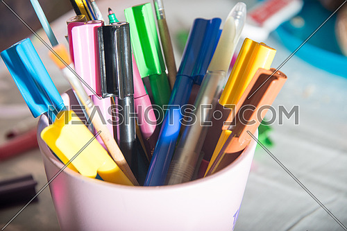 coloring markers in a pink bucket